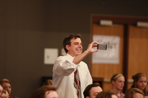 Adviser takes photo during awards presentation.