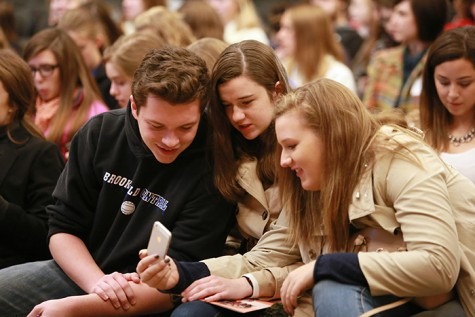 Brookfield Central High School students check cell phone for information.